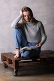 Κορίτσι συνεδρίασης με ένα βιβλίο Γκρίζα ανασκόπηση Στοκ Φωτογραφία