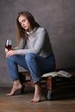 Κορίτσι συνεδρίασης με τις ιδιαίτερες προσοχές που κρατά το ποτήρι του κρασιού Γκρίζα ανασκόπηση Στοκ Εικόνες