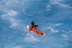κορίτσι σύλληψης που κωπηλατεί surfer στο κύμα Στοκ Φωτογραφίες