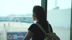 Κορίτσι ταξιδιού που στέκεται στο παράθυρο στο τερματικό αερολιμένων απόθεμα βίντεο