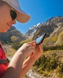 Κορίτσι-ταξιδιωτική χρησιμοποίηση κινητή στα βουνά Στοκ Εικόνες