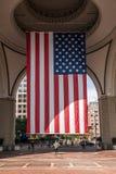 04 09 2017 κορίτσι της Βοστώνης Μασαχουσέτη ΗΠΑ που στέκεται κάτω από μια μεγάλη αμερικανική σημαία λωρίδων αστεριών που κρεμά απ Στοκ φωτογραφία με δικαίωμα ελεύθερης χρήσης