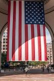 04 09 2017 κορίτσι της Βοστώνης Μασαχουσέτη ΗΠΑ που στέκεται κάτω από μια μεγάλη αμερικανική σημαία λωρίδων αστεριών που κρεμά απ Στοκ φωτογραφίες με δικαίωμα ελεύθερης χρήσης