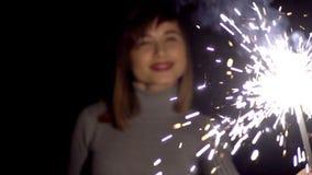 Κορίτσι της καυκάσιας εμφάνισης με ένα χαμόγελο στην εκμετάλλευση προσώπου του στα χέρια του ένα Sparkler απόθεμα βίντεο