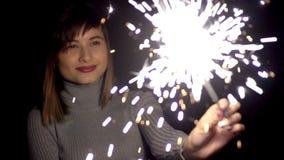 Κορίτσι της καυκάσιας εμφάνισης σε μια γκρίζα πλεκτή εκμετάλλευση και την οδήγηση πουλόβερ από τη μία πλευρά στην άλλη Sparkler,  απόθεμα βίντεο