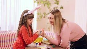 Κορίτσι της καυκάσιας εμφάνισης στα χέρια που κρατούν ένα αυγό Πάσχας, αλλά αυτή τη φορά η κόρη της με ένα διαθέσιμο χρώμα χεριών απόθεμα βίντεο