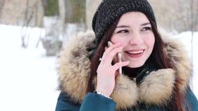Κορίτσι της Νίκαιας που μιλά με κινητό τηλέφωνο στο χειμερινό πάρκο απόθεμα βίντεο