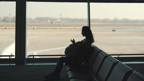 Κορίτσι τουριστών με ένα σακίδιο πλάτης που περιμένει μια πτήση απόθεμα βίντεο