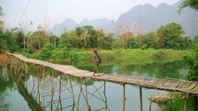 Κορίτσι τουριστών που περπατά στη γέφυρα μπαμπού, vang vieng, Λάος απόθεμα βίντεο