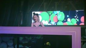 Κορίτσι του DJ στα αυτιά ποντικιών που περιστρέφουν και που χαμογελούν στην περιστροφική πλάκα λέσχη κίνηση αργή απόθεμα βίντεο