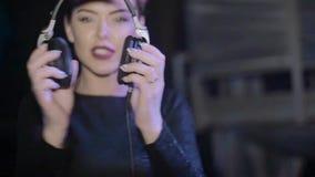 Κορίτσι του DJ στα μαύρα τοπ ακουστικά βρόντου στην περιστροφική πλάκα nightclub κίνηση αργή απόθεμα βίντεο