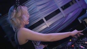 Κορίτσι του DJ στην καμμένος κορυφή, αυτιά ποντικιών που περιστρέφει στην περιστροφική πλάκα nightclub κίνηση αργή απόθεμα βίντεο