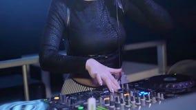 Κορίτσι του DJ στην κορυφή που αναμιγνύει στην περιστροφική πλάκα, χαμόγελο nightclub Ακουστικά κίνηση αργή φιλμ μικρού μήκους