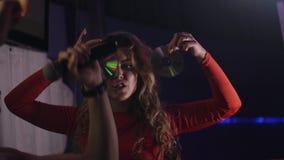 Κορίτσι του DJ στον κόκκινο δίσκο του CD κυμάτων φορεμάτων στο πρόσωπο στο νυχτερινό κέντρο διασκέδασης Φανείτε κεκλεισμένων των  φιλμ μικρού μήκους