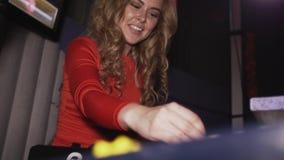 Κορίτσι του DJ στο κόκκινο φόρεμα με το πλαίσιο στην επικεφαλής περιστροφή στην περιστροφική πλάκα στη λέσχη Χαμόγελο απόθεμα βίντεο