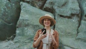 Κορίτσι το πολύ όμορφο και της Νίκαιας στο καπέλο κάνει Selfie κοντά στους βράχους Γυναίκα που χαμογελά και που φωτογραφίζεται στ απόθεμα βίντεο