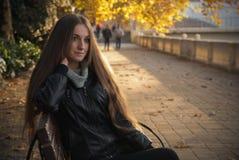 Κορίτσι το υπόβαθρο φθινοπώρου πάγκων με τα κίτρινα φύλλα επάνω Στοκ Εικόνες