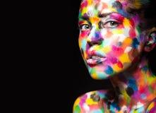 Κορίτσι το χρωματισμένο πρόσωπο που χρωματίζεται με Εικόνα ομορφιάς τέχνης Στοκ Εικόνα