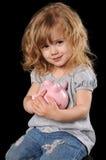 κορίτσι τραπεζών που κρατά τις piggy νεολαίες Στοκ Εικόνες