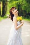 Κορίτσι υπαίθρια με τα λουλούδια στοκ φωτογραφία