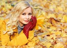 Κορίτσι φθινοπώρου. Ξανθή όμορφη γυναίκα μόδας με τα φύλλα σφενδάμου μέσα Στοκ Εικόνες