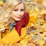 Κορίτσι φθινοπώρου. Ξανθή όμορφη γυναίκα μόδας με τα φύλλα σφενδάμου μέσα Στοκ Φωτογραφία
