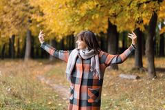 Κορίτσι φθινοπώρου που περπατά στο πάρκο πόλεων Πορτρέτο της ευτυχούς καλής και όμορφης νέας γυναίκας στο δάσος στα χρώματα πτώση Στοκ Φωτογραφίες