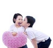 Κορίτσι φιλιών αγοριών με το μαξιλάρι καρδιών - που απομονώνεται Στοκ Εικόνες