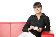κορίτσι φλυτζανιών καφέ που έχει τον καναπέ υπολοίπου Στοκ εικόνες με δικαίωμα ελεύθερης χρήσης