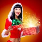 Κορίτσι χιονιού με ένα δώρο Χριστουγέννων με μαγικό να λάμψει Στοκ Φωτογραφίες