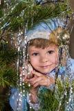 Κορίτσι χιονιού μικρών κοριτσιών σε ένα υπόβαθρο του χριστουγεννιάτικου δέντρου στοκ φωτογραφία