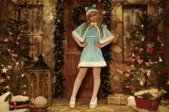 Κορίτσι χιονιού στο κατώφλι του σπιτιού που διακοσμείται στο ύφος Χριστουγέννων Στοκ Εικόνες