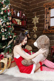 Κορίτσι χιονιού στο κόκκινο φόρεμα με την αρκούδα στο υπόβαθρο χριστουγεννιάτικων δέντρων Στοκ Εικόνες
