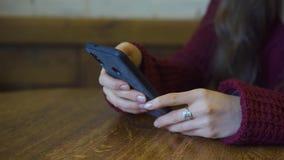 Κορίτσι χρησιμοποιώντας το smartphone app και χαμογελώντας στον καφέ Κλείστε αυξημένος νέος περιστασιακός θηλυκός επαγγελματίας σ απόθεμα βίντεο