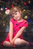 Κορίτσι Χριστουγέννων μπροστά από το χριστουγεννιάτικο δέντρο Στοκ εικόνα με δικαίωμα ελεύθερης χρήσης