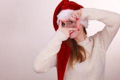Κορίτσι Χριστουγέννων που κάνει τη χειρονομία πλαισίων δάχτυλων Στοκ Εικόνα