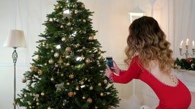 Κορίτσι Χριστουγέννων που φωτογραφίζεται σε ένα κινητό τηλεφωνικό χριστουγεννιάτικο δέντρο με τα παιχνίδια, όμορφο χριστουγεννιάτ απόθεμα βίντεο