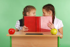 Κορίτσι δύο σχολείων που μοιράζεται τα μυστικά που κάθονται σε ένα γραφείο από το βιβλίο Στοκ Φωτογραφίες