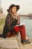 Κορίτσι Brunette με ένα βιβλίο από την όχθη ποταμού στοκ εικόνα με δικαίωμα ελεύθερης χρήσης