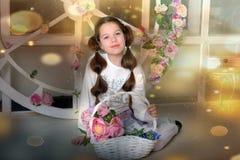 Κορίτσι Brunette με ένα ψάθινο καλάθι με τα λουλούδια στοκ εικόνες