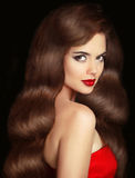 Κορίτσι Brunette με τη μακριά λαμπρή κυματιστή τρίχα και τα κόκκινα χείλια makeup μπαζούκας Στοκ Φωτογραφία