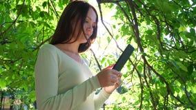 Κορίτσι Brunette που κοιτάζει βιαστικά στο smartphone, που στέκεται ενάντια στο φωτεινό ήλιο φιλμ μικρού μήκους