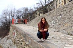 Κορίτσι Brunette που φορά το σακάκι δέρματος, το τζιν παντελόνι και τα ρόδινα πάνινα παπούτσια Στοκ εικόνα με δικαίωμα ελεύθερης χρήσης