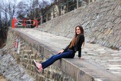 Κορίτσι Brunette που φορά το σακάκι δέρματος, το τζιν παντελόνι και τα ρόδινα πάνινα παπούτσια Στοκ εικόνες με δικαίωμα ελεύθερης χρήσης