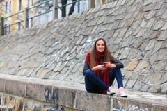 Κορίτσι Brunette που φορά το σακάκι δέρματος, το τζιν παντελόνι και τα ρόδινα πάνινα παπούτσια Στοκ Φωτογραφία