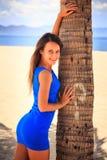 κορίτσι brunette στα μπλε χαμόγελα φοινικών αφών ενάντια στην άμμο Στοκ Εικόνα