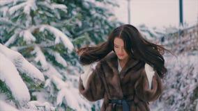 Κορίτσι Brunette στις καφετιές βούρτσες παλτών γουνών που περπατά στο χειμώνα σε αργή κίνηση φιλμ μικρού μήκους