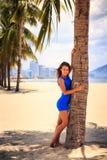 κορίτσι brunette στον μπλε ξυπόλυτο φοίνικα αφών ενάντια στη σειρά φοινικών Στοκ φωτογραφίες με δικαίωμα ελεύθερης χρήσης