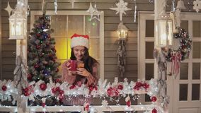 Κορίτσι Brunette στο καπέλο Άγιου Βασίλη που στέλνει το χαιρετισμό sms που χρησιμοποιεί το έξυπνο τηλέφωνο ένα μέρος απόθεμα βίντεο