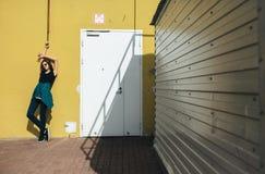 Κορίτσι Brunette στο μαύρο ύφος βράχου, που στέκεται ενάντια στον κίτρινο τοίχο υπαίθρια στην οδό πόλεων Στοκ εικόνες με δικαίωμα ελεύθερης χρήσης